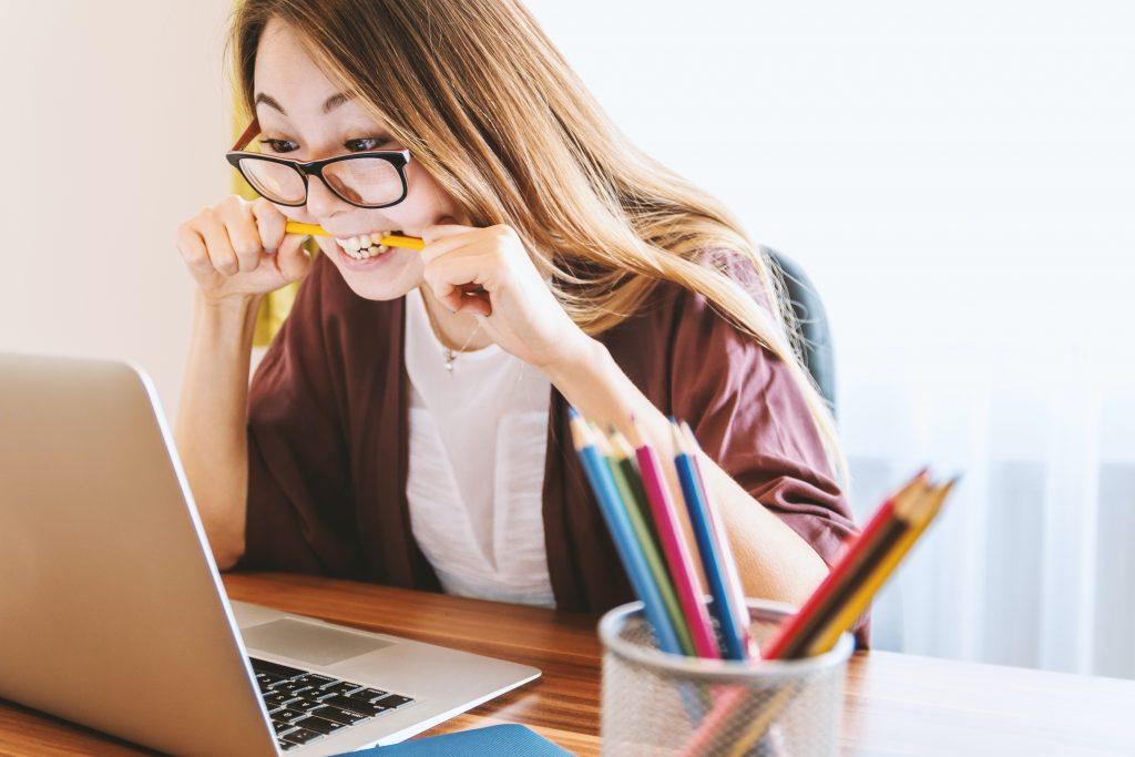 mulher sentada à frente do computador estudando