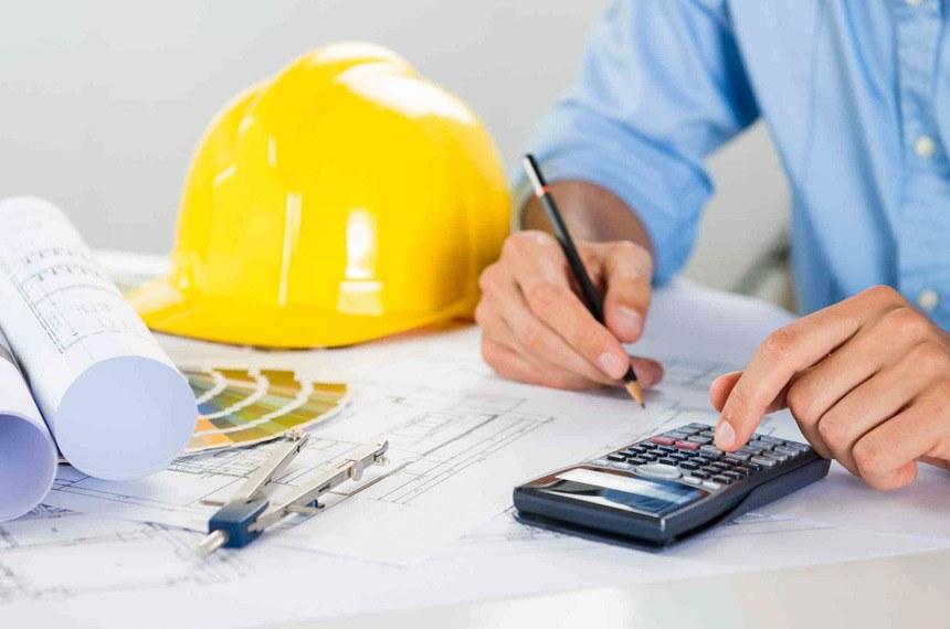mãos fazendo cálculo em calculadora ao lado de capacete de engenharia