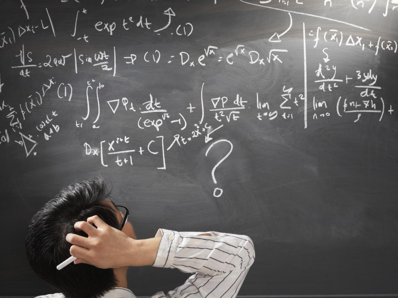 homem escrevendo equação matemática em quadro negro e com dúvida