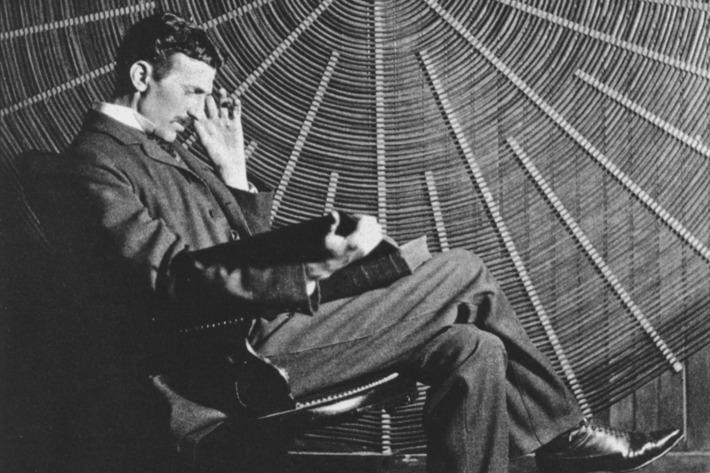 Nikola Tesla em imagem em preto e branco segurando um livro