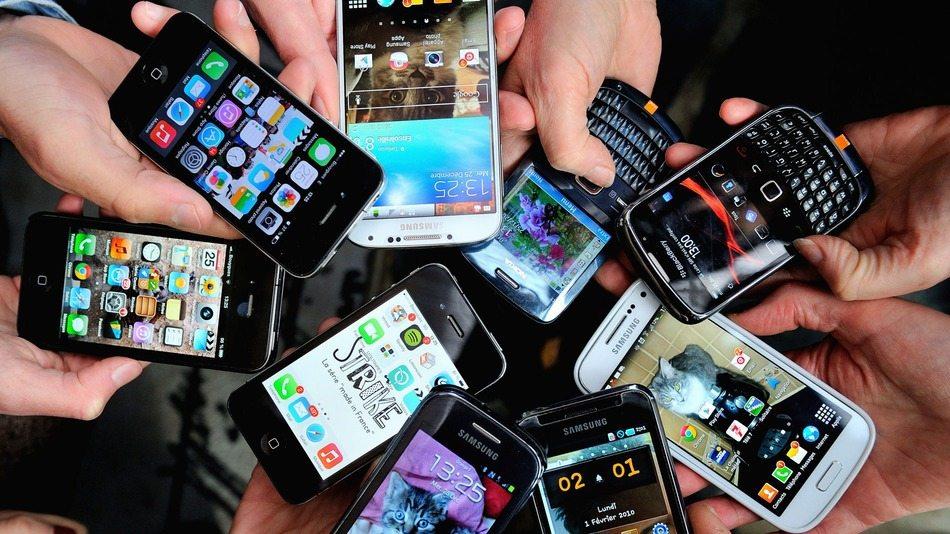 Imagem de vários celulares nas palmas das mãos de diferentes pessoas