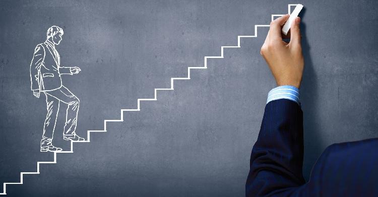 Imagem de gráfica de escada sendo desenha por uma mão, com giz na lousa, e homem subindo as escadas em desenho gráfico na lousa