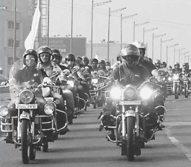 Imagem antiga de motociclistas em motos Royal Enfield, enfileirados na estrada