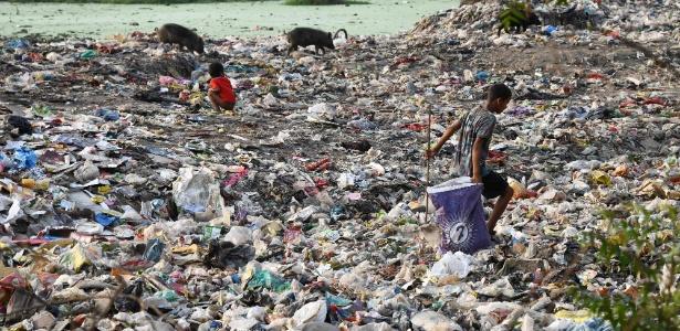 Imagem de grande quantidade de lixo na Índia e crianças em meio ao lixo. Plástico Reciclado