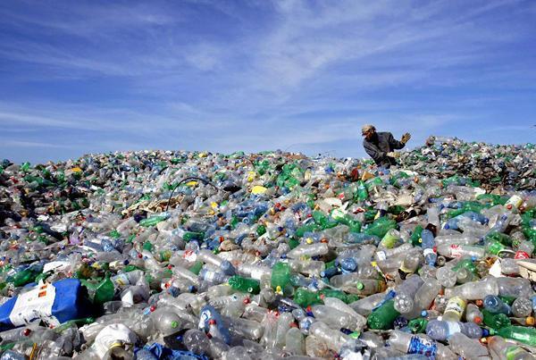Imagem de milhares de garrafas de plástico em lixão e homem ao fundo - Plástico Reciclado