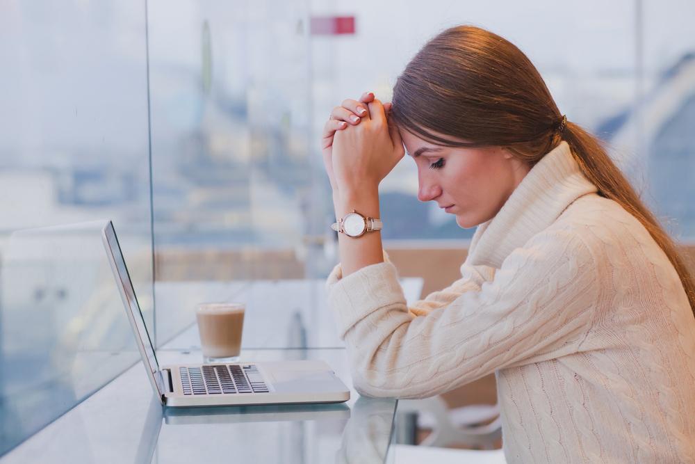 mulher sentada lamentando na frente de computador