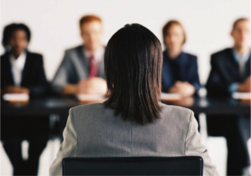 mulher sentada ao centro de mesa de entrevista de emprego, de costas para a imagem e de frente para quatro recrutadores