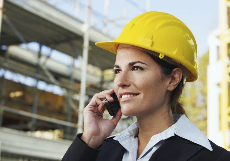 Imagem ilustrativa de mulher engenheira falando ao telefone, com obra ao fundo.