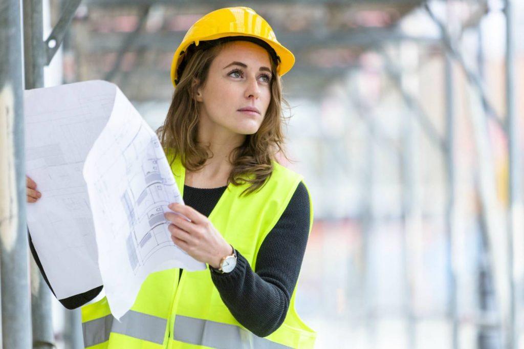 Imagem ilustrativa de mulher branca segurando planta e usando capacete de engenheira, representando mulheres em gerenciamento de obras.