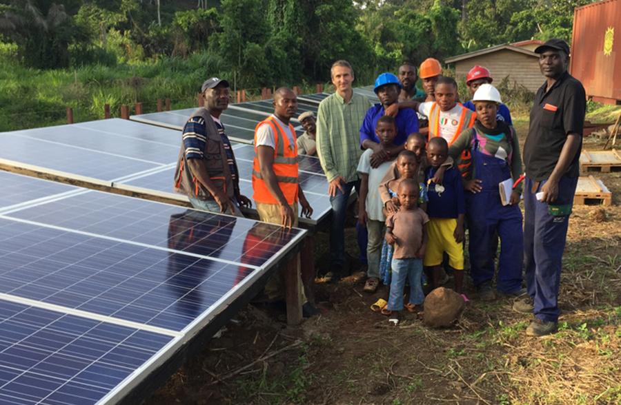 equipe de jovens e adultos ao lado de placas de energia fotovoltaica