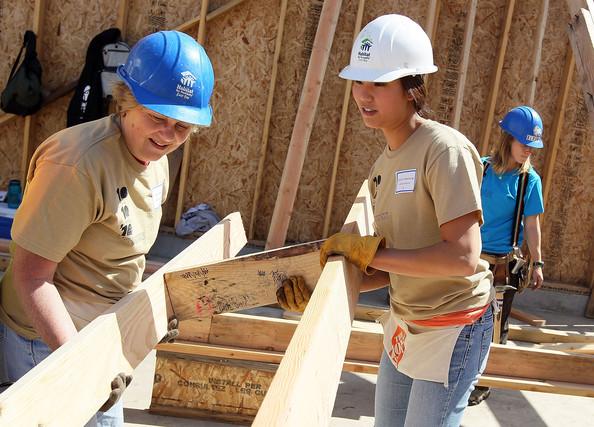 duas mulheres com capacete de engenharia ajudando a carregar madeiras em projeto de engenharia humanitária
