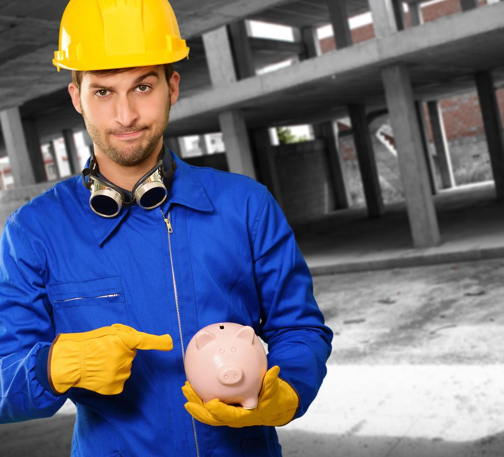 homem engenheiro segurando um cofre de porquinho
