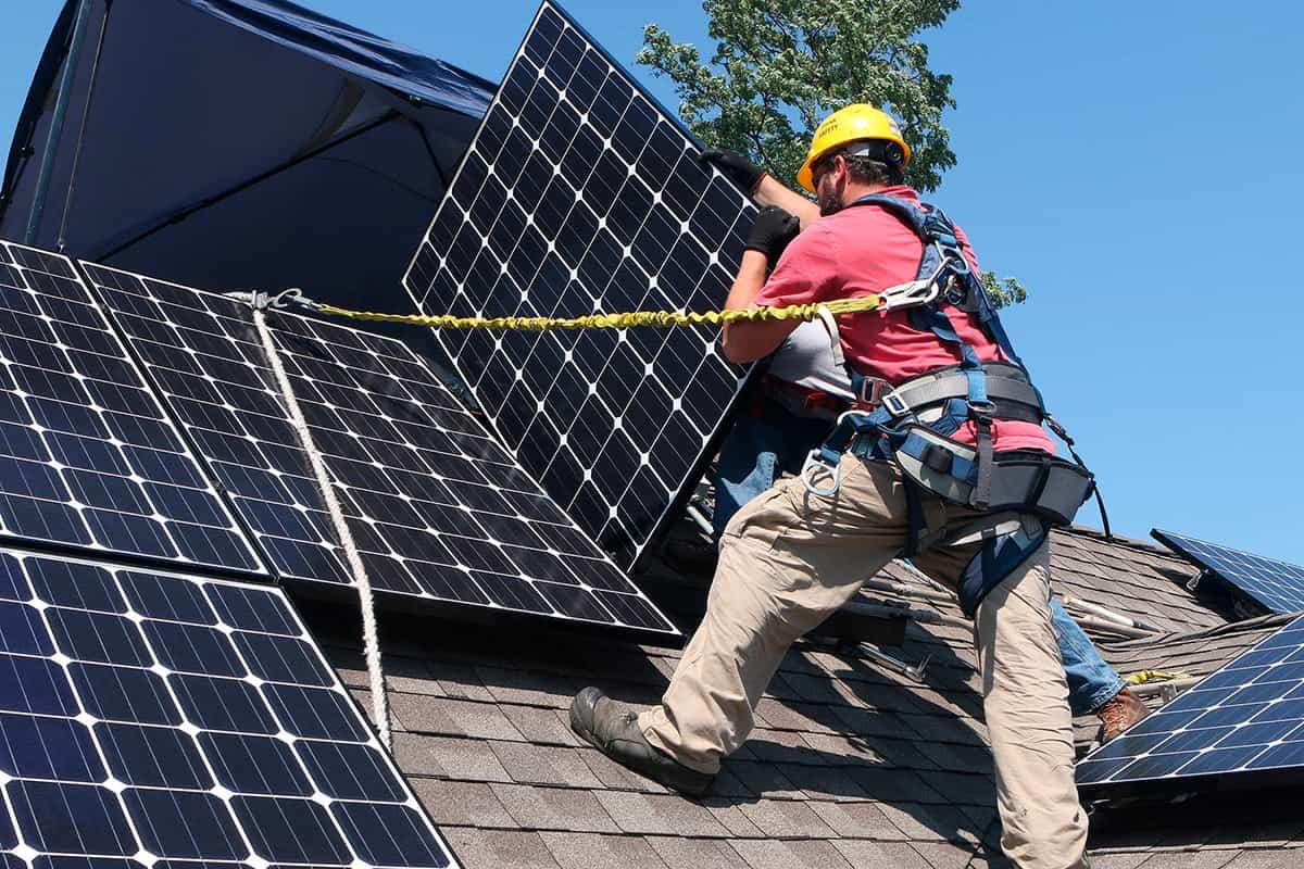 Homem fazendo instalação de painéis solares