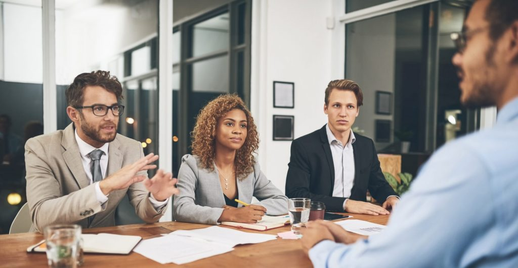 três homens e uma mulher em entrevista de emprego