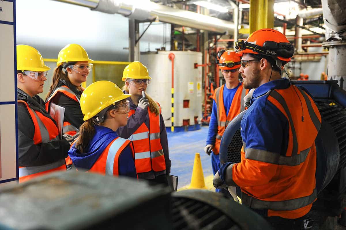 Grupo de pessoas conversando com equipamentos de EPI