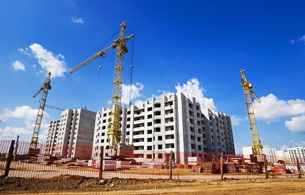 Imagem de obra de edifícios em andamento, com três guindastes e céu azul ao fundo