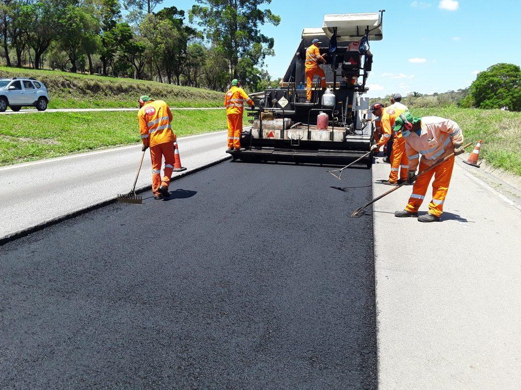 Funcionários em obra de pavimentação, colocando asfalto na pista