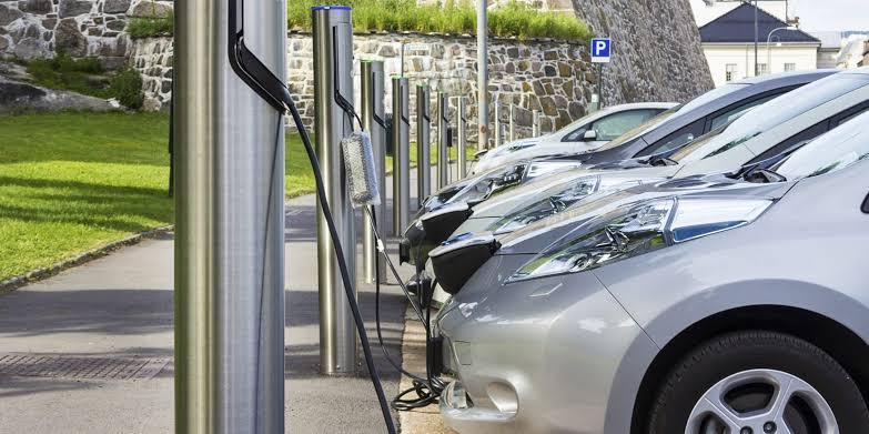 carros elétricos na cor prata enfileirados conectados a terminais de recarga