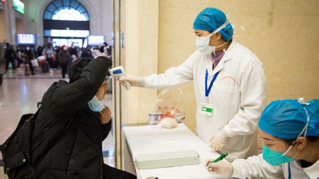 Médicos chineses verificando febre em paciente suspeito de coronavirus em hospital na China