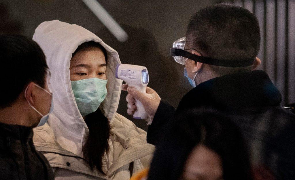 mulher usando máscara descartável no rosto para evitar coronavírus tendo temperatura aferida