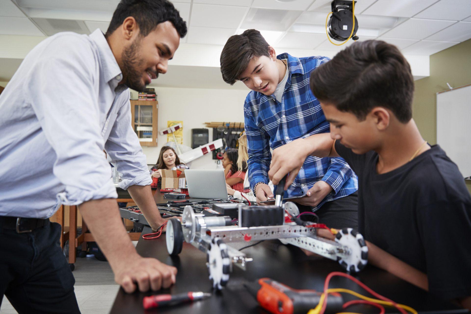 professor auxiliando dois alunos a construir um protótipo robótico