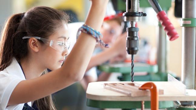 mulher estudante de engenharia manipulando máquina para furar madeira