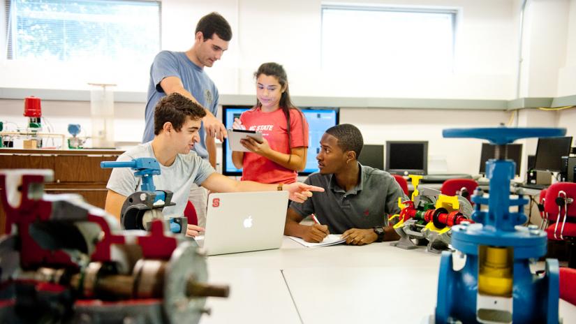 Dois alunos de pé tirando dúvidas e dois alunos sentados usando computador