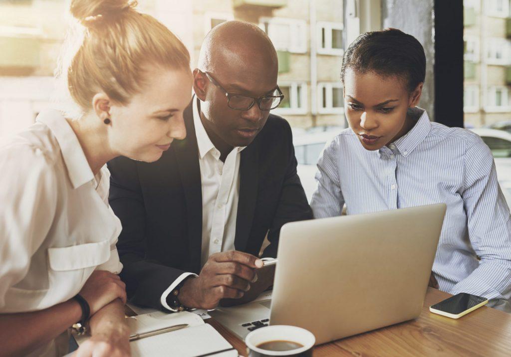 duas mulheres e um homem olhando para a tela de um notebook vagas de engenharia durante entrevista de emprego