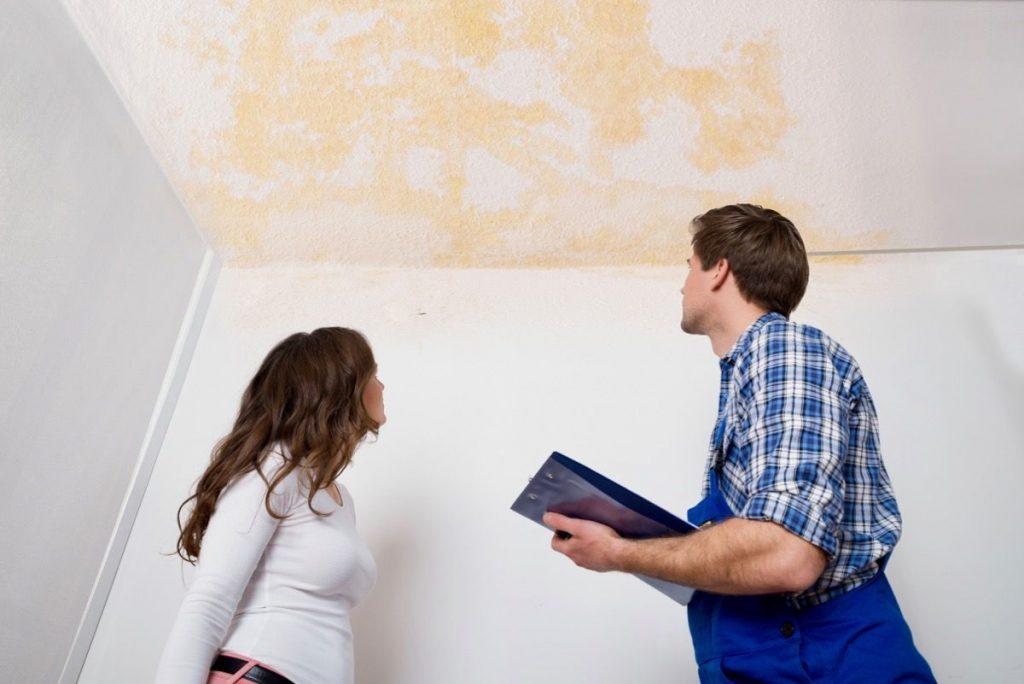 Homem e mulher olhando para teto branco com infiltração vícios construtivos