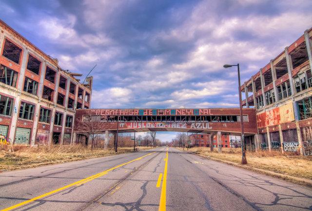 Vista de uma rua com prédios abandonados nas laterais.