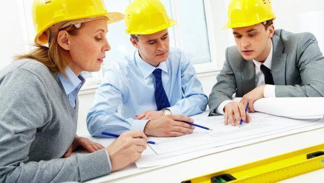 Três engenheiros com capacete amarelo sentados em ao redor de uma mesa analisando um projeto.