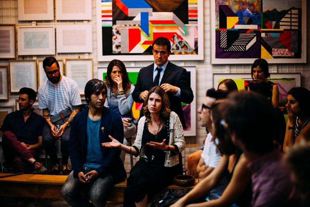 Mulher falando e gesticulando para um grupo de pessoas. Habilidades de comunicação. Engenharia 360.