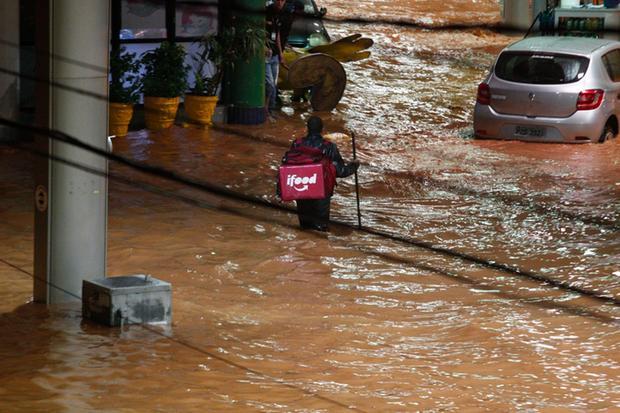 Homem com entrega do ifood caminhando em rua alagada em Belo Horizonte