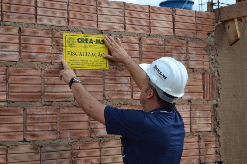 homem pregando placa de fiscalização do CREA em muro de obra