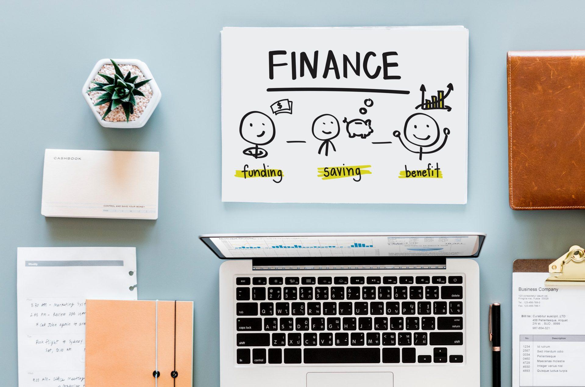 mesa com notebook, livros e papel com desenho sobre educação financeira