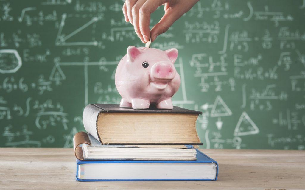 cofre de porquinho em cima de livros com quadro negro com equações ao fundo
