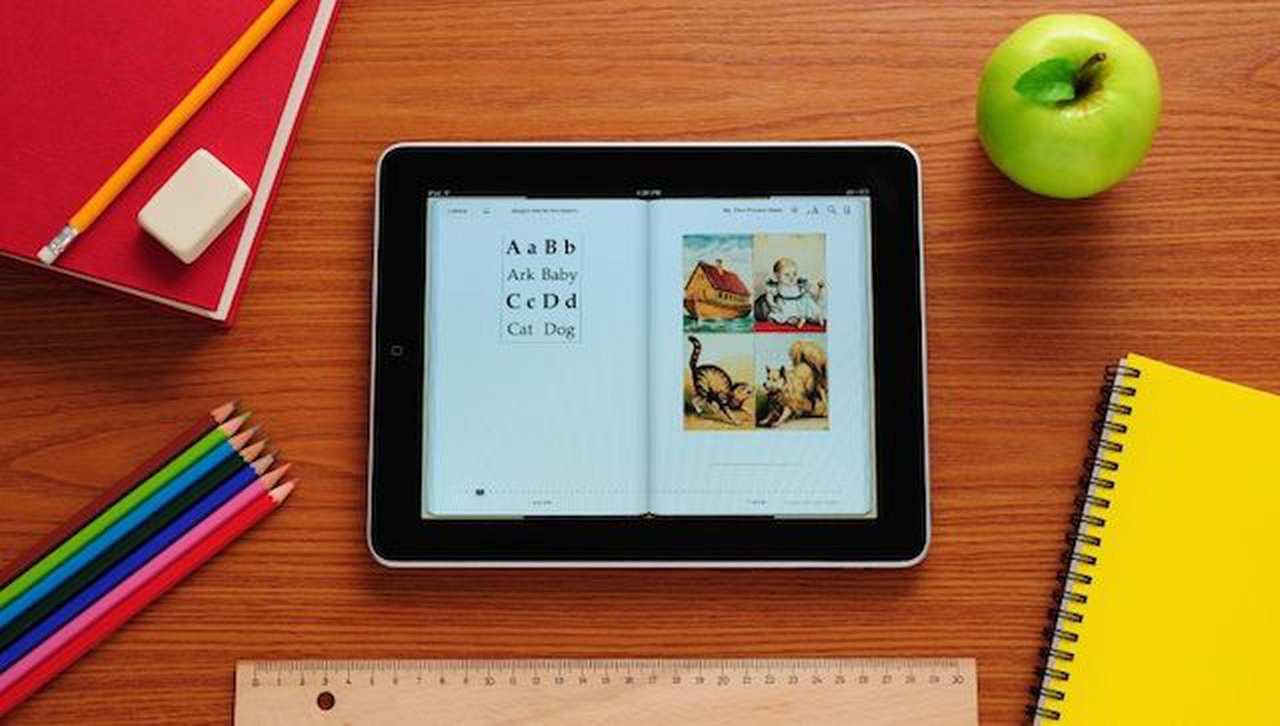 iPad em cima de mesa de professor, com agenda, maçã e lápis