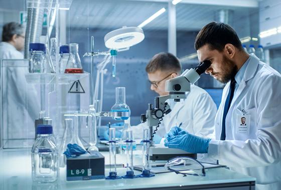 Imagem de dois cientistas apoiados numa bancada dentro de um laboratório. Na imagem há vidrarias e equipamentos de laboratório