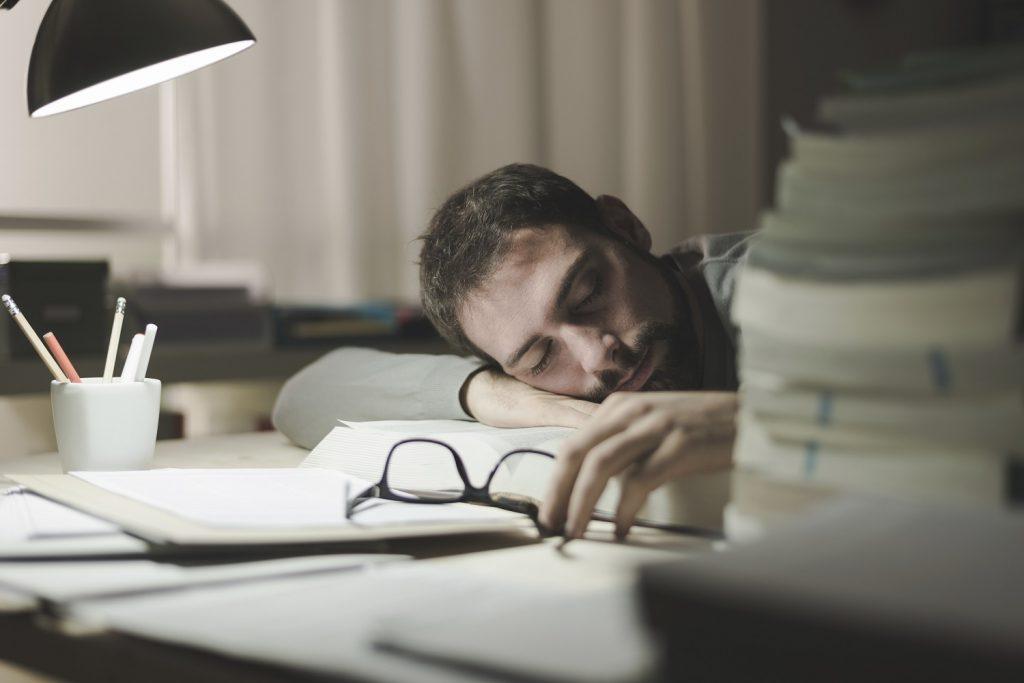 homem jovem dormindo em sua mesa enquanto estuda