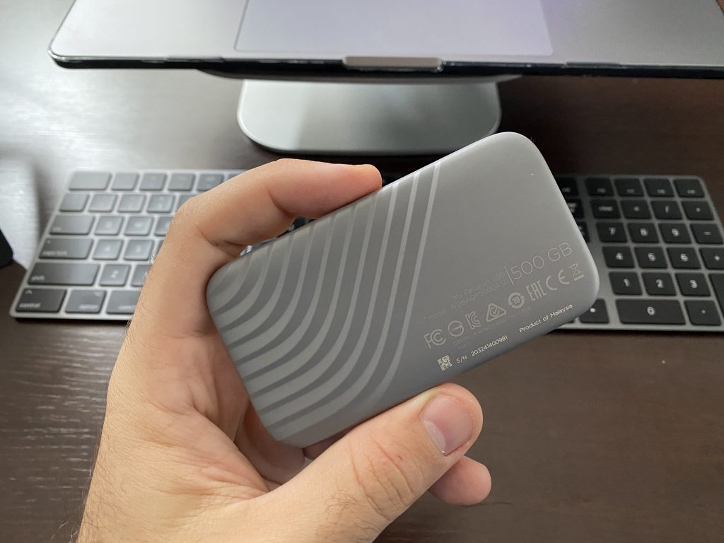 mão segurando SSD my passport western digital em frente a computador