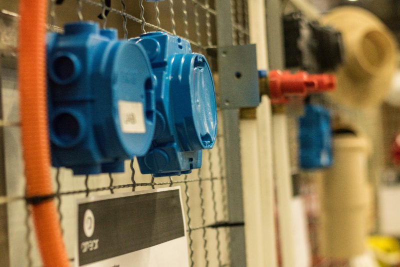 Componentes de instalações elétricas (eletrodutos e caixas de derivação) fixados em grade.