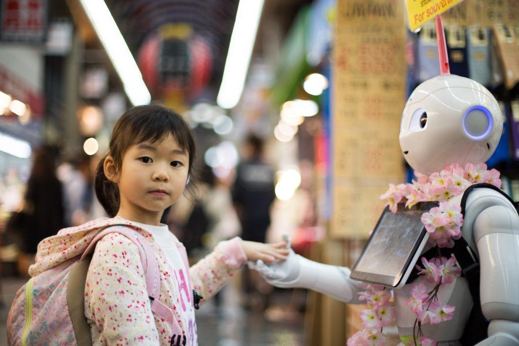 Criança em Osaka interagindo com um robô. Foto:  Andy Kelly via Unsplash.