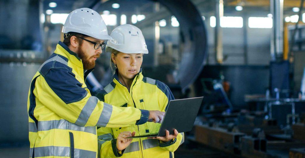 engenheiros em fábrica olhando para computador