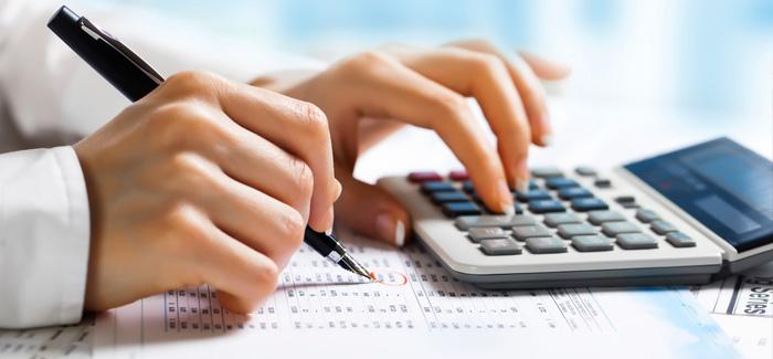 mãos usando calculadora e escrevendo em planilha de custos