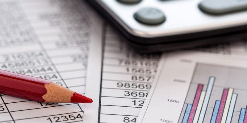 lápis, calculadora e planilha de custos