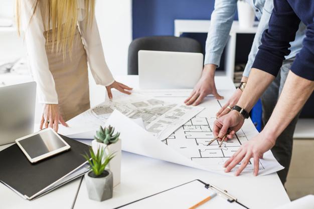 Mãos de pessoas em uma mesa analisando e apontando para folhas de projetos.