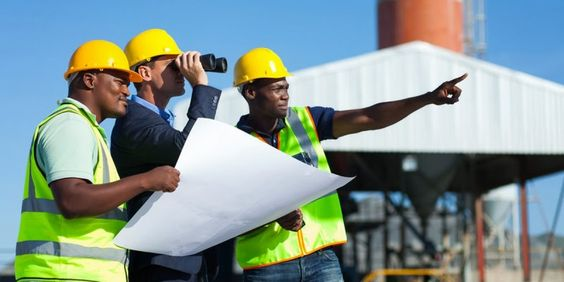 Homens de capacete em canteiro de obra olhando para a mesma direção.