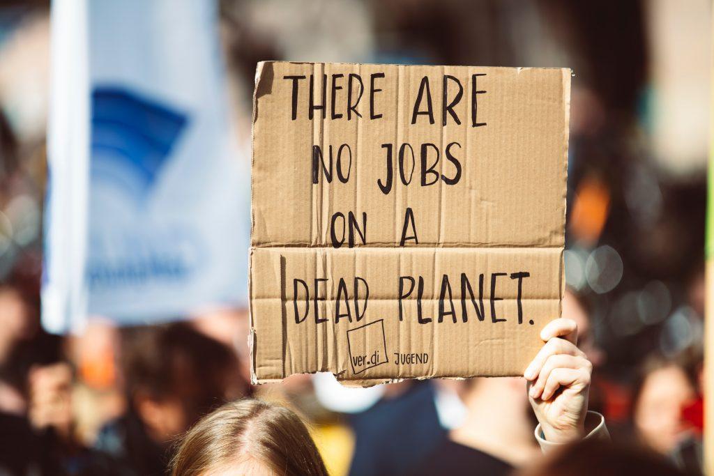 """MIT 10 - Placa em papelão, com a frase """"não há empregos em um planeta morto"""", em inglês. Foto: Markus Spiske via Unsplash."""