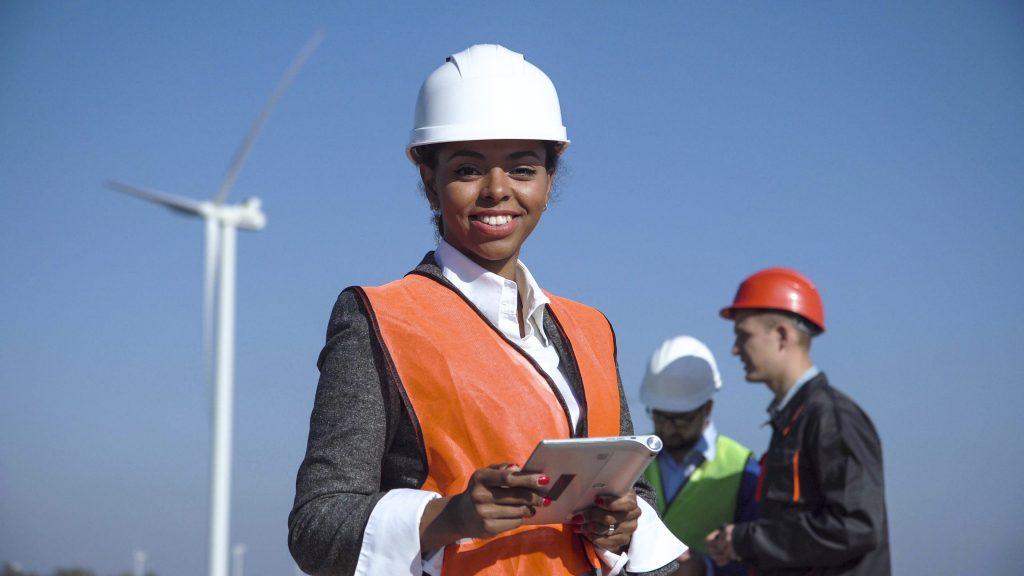 Imagem de mulher engenheira olhando para câmera, com fundo com dois homens engenheiros próximos à turbina eólica. Representa mulheres na engenharia