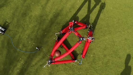 Visão aérea do robô isoperimétrico segurando e segurando uma bola de basquete.